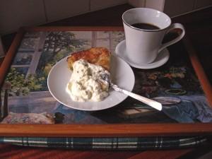 Rabarberkaka med en klick grädde och en kopp kaffe